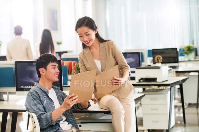 Молодых профессиональных азиатских бизнесменов, работающих с блокнотов и бумаг в офисе — стоковое фото