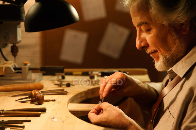 Side view of smiling mature jewelry designer in apron working with ring in workshop — Stock Photo