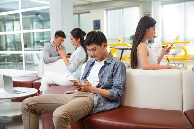 Giovani asiatici seduti e utilizzando smartphone in ufficio moderno — Foto stock