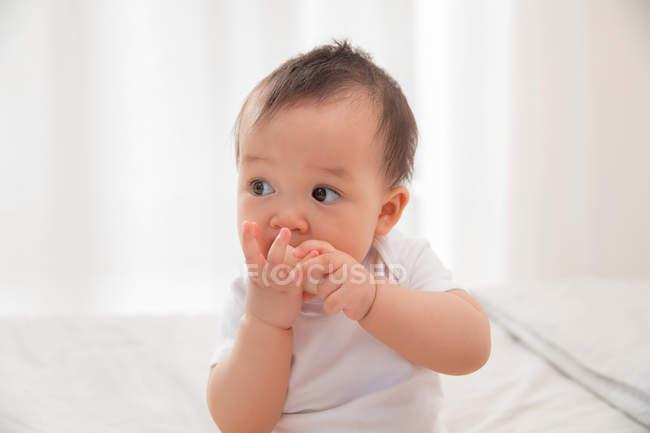 Schöne asiatische Säugling Kind isst Stück geschälte Früchte und schaut weg zu Hause — Stockfoto