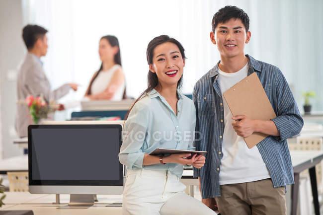 Happy молоді азіатські і підприємець тримає буфер обміну і цифровий планшет, стоячи разом і посміхається в камері в офісі — стокове фото