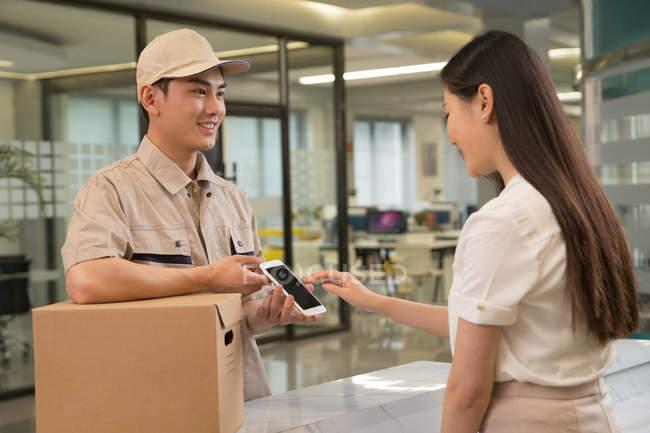 Улыбающийся молодой азиатский курьер с картонной коробкой глядя на деловую женщину с помощью смартфона в офисе — стоковое фото