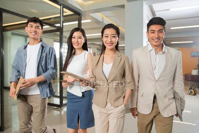Jeunes professionnels asiatiques gens d'affaires debout avec des presse-papiers et souriant à la caméra dans le bureau — Photo de stock