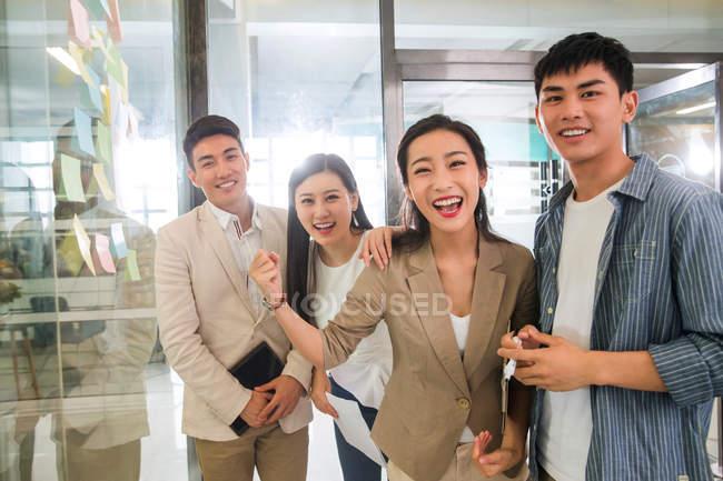 Веселої молоді азіатські бізнес команди працюють разом і посміхатися камери в офісі — стокове фото