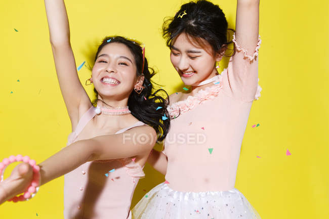 Beautiful happy stylish asian girlfriends having fun and dancing on yellow background with colorful confetti — Stock Photo