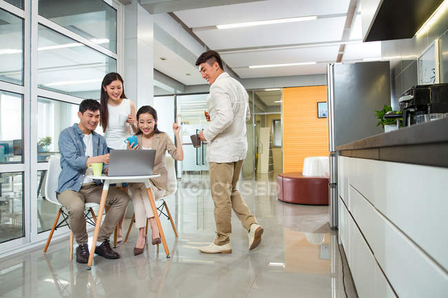 Young asian business colleagues holding cups and using laptop during coffee break — Stock Photo
