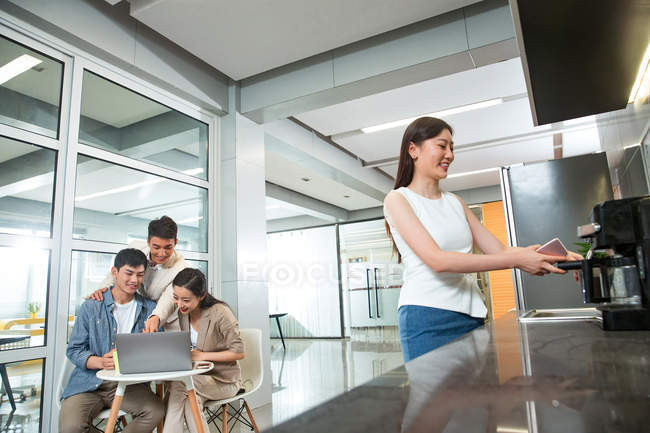 Smiling young asian businesswoman making coffee while colleagues working with laptop behind in office — Stock Photo