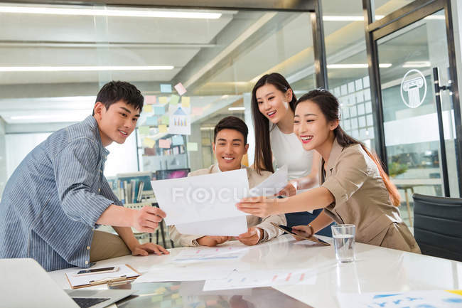Professional smiling young asian business team working with papers in modern office — Stock Photo