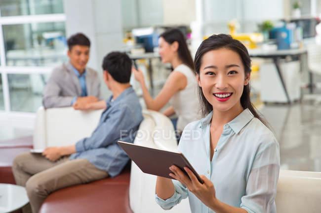Attrayant heureux jeune asiatique femme d'affaires en utilisant tablette numérique et souriant à la caméra dans le bureau — Photo de stock
