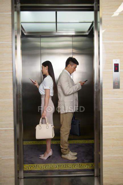 Vista laterale di giovane uomo d'affari asiatico e donna d'affari in piedi back to back e utilizzando smartphone in ascensore — Foto stock