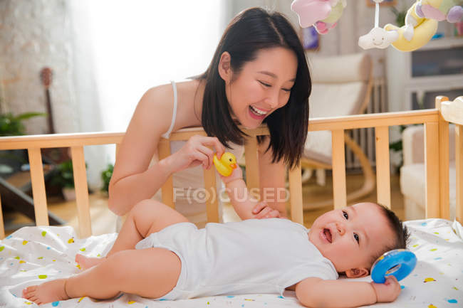 Happy young mother looking at adorable baby lying in crib and playing with rubber toys — Stock Photo