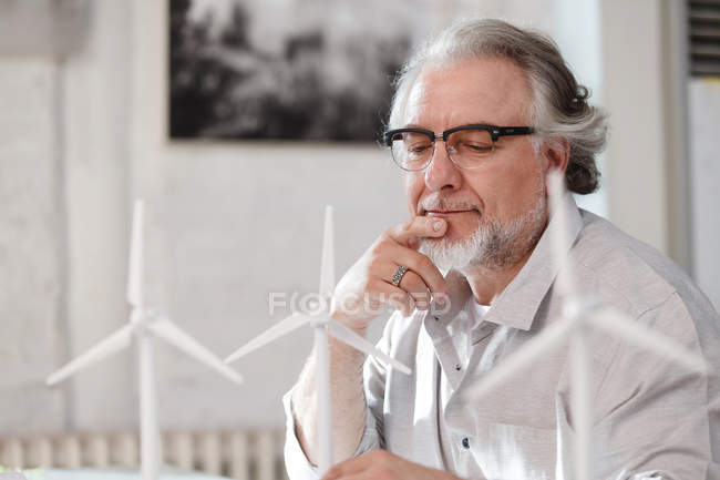 Bearded mature architect in eyeglasses working with wind turbines in office — Stock Photo