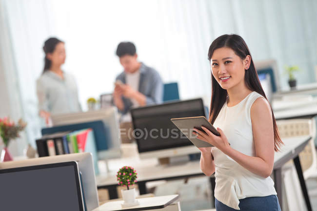 Beautiful young businesswoman holding digital tablet and smiling at camera in office — Stock Photo