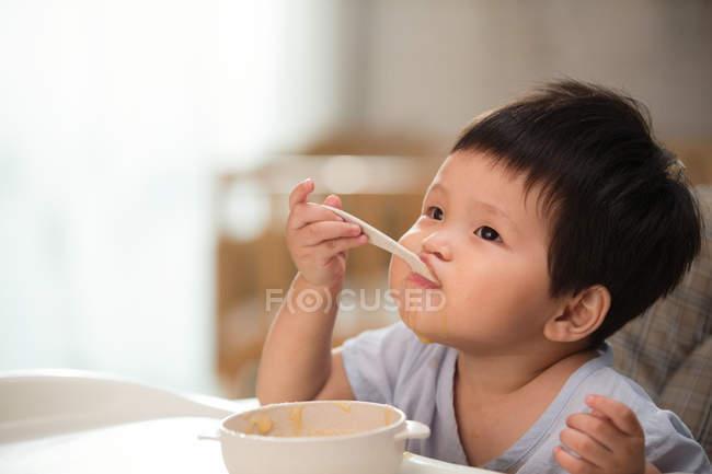 Entzückende asiatische Kleinkind essen mit Löffel und suchen nach oben zu Hause — Stockfoto