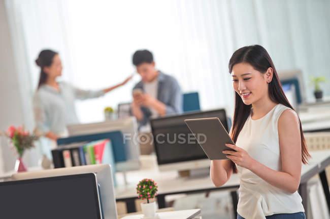 Красива посміхаючись молода Ділова жінка з використанням цифрових планшетів, колег, що працюють позаду в офісі — стокове фото