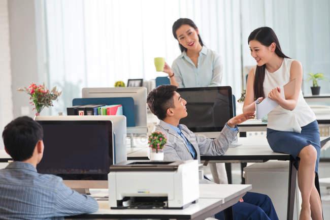 Bel homme d'affaires asiatique parlant avec des collègues féminines souriantes dans le bureau moderne — Photo de stock