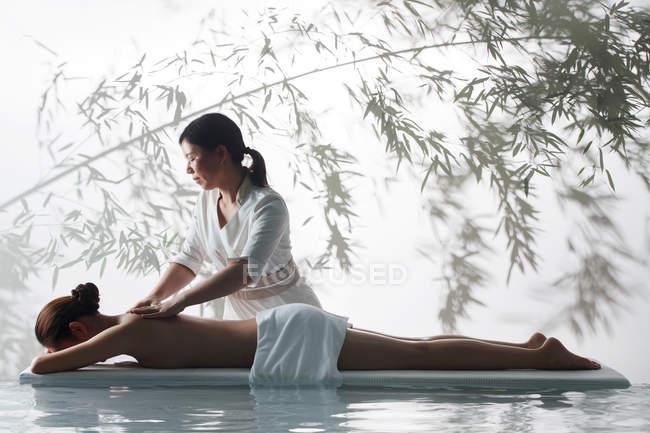 Вид сбоку на массажистку, делающую массаж тела молодой женщине в спа — стоковое фото