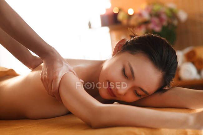Close-up view of beautiful young asian woman with closed eyes receiving massage in spa, cropped shot — Stock Photo