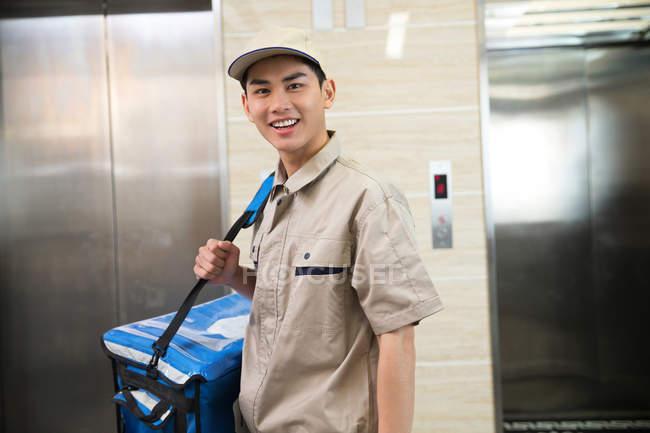 Bonito jovem ásia entrega homem com saco sorrindo para câmara no escritório — Fotografia de Stock