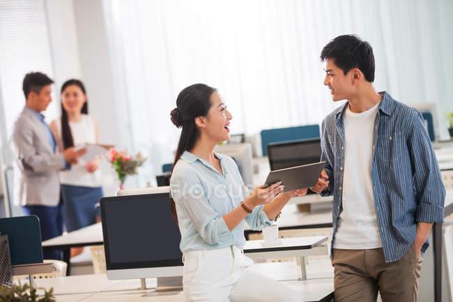 Улыбается молодой бизнесмен и предприниматель с помощью цифрового планшета и обсуждение работы в офисе — стоковое фото