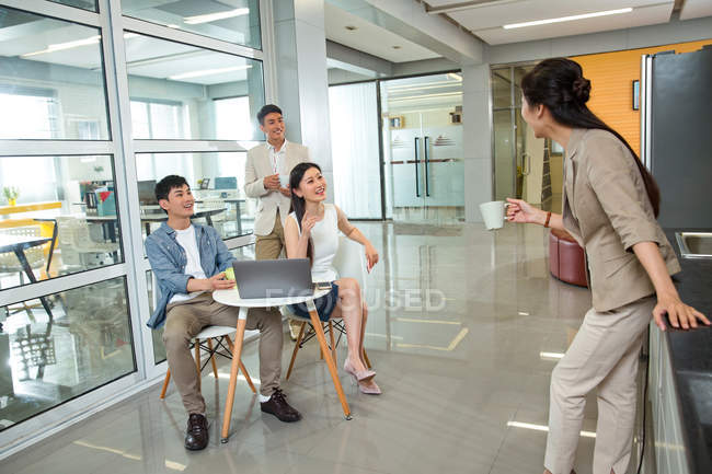 Молодая деловая женщина держит чашку кофе и смотрит на улыбающихся коллег, использующих ноутбук в офисе — стоковое фото