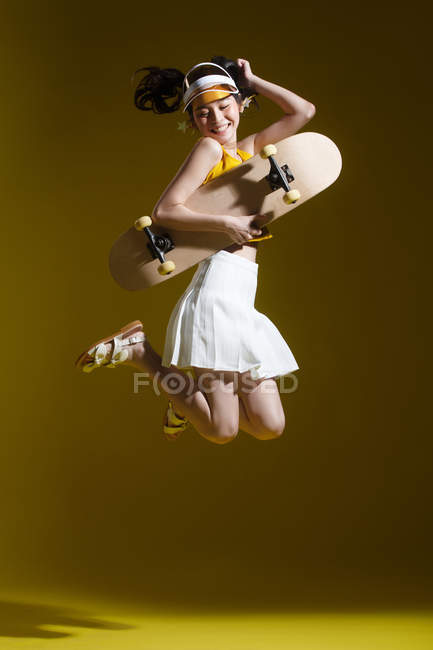 Full length view of beautiful happy asian girl holding skateboard and jumping in studio — Stock Photo