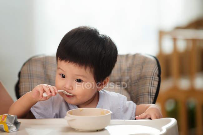 Niedliche asiatische Kleinkinder halten Löffel und essen zu Hause — Stockfoto