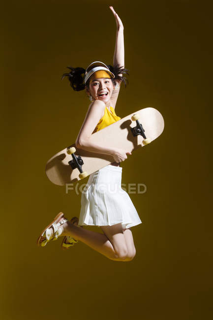 Attractive happy asian girl in transparent cap holding skateboard and jumping in studio — Stock Photo