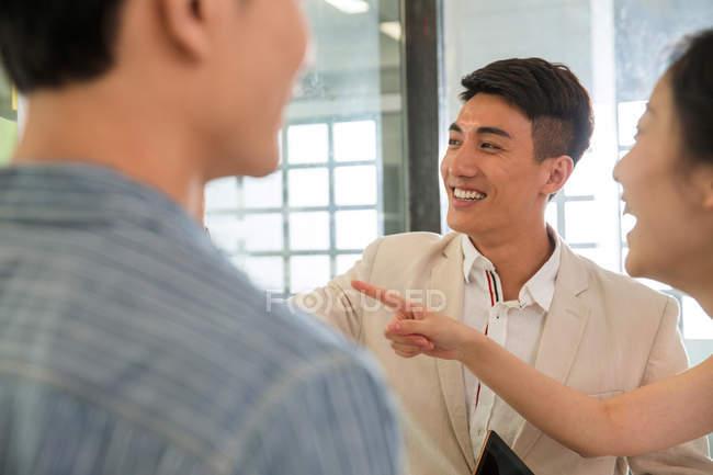 Обрізаний постріл щасливих молодих бізнесменів і бізнес-леді сміючись в офісі — стокове фото