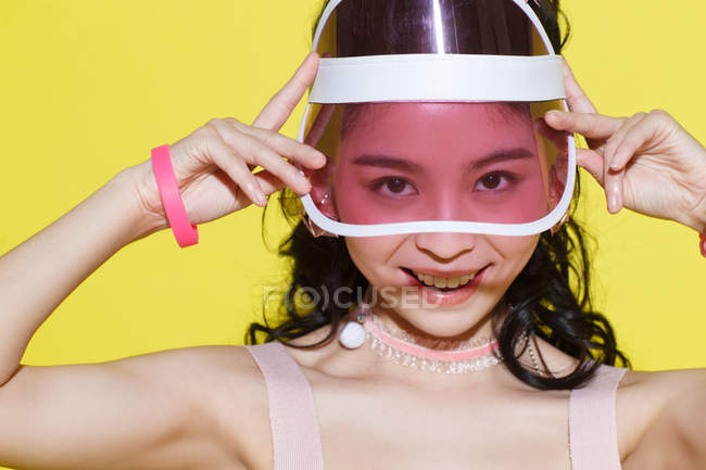 Beautiful happy asian girl adjusting cap and smiling at camera isolated on yellow — Stock Photo