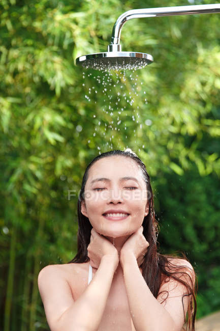Front view of beautiful smiling asian girl taking shower with closed eyes — Stock Photo