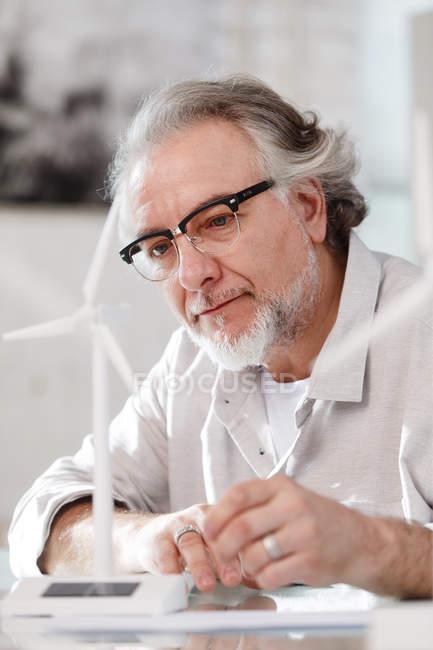 Professionnel concentré architecte mature dans les lunettes de travail avec le modèle moulin à vent dans le bureau — Photo de stock