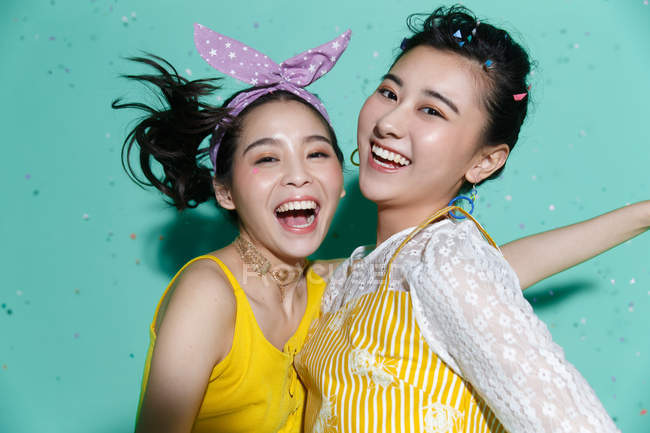 Beautiful happy stylish asian girlfriends having fun and dancing on blue background with colorful confetti — Stock Photo
