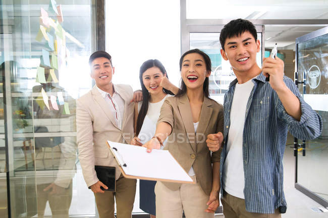 Cheerful young asian business team working together and smiling at camera in office — Stock Photo