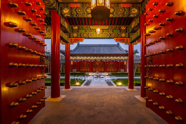 View through the gates at beautiful traditional asian architecture with red columns and green plants in yard — Stock Photo