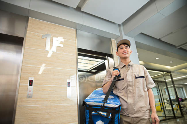 Low angle view of smiling young asian delivery man with bag standing near elevator in office — Stock Photo