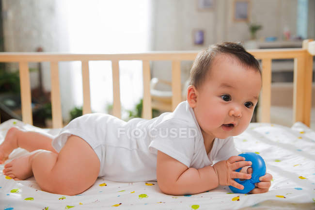 Side view of adorable asian baby lying in crib and playing with blue toy — Stock Photo