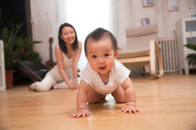 Очаровательны счастливый Азиатский ребенок ползет по полу и, глядя на камеру, улыбаясь молодая мать сидит у себя дома — стоковое фото