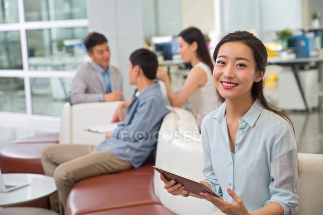 Красивая молодая азиатская бизнесвумен держит цифровой планшет и улыбается в камеру, в то время как коллеги работают в офисе — стоковое фото