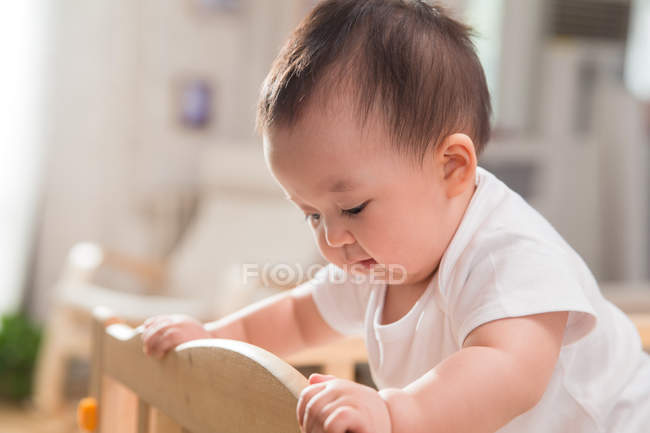 Side view of adorable asian infant standing and leaning at crib — Stock Photo