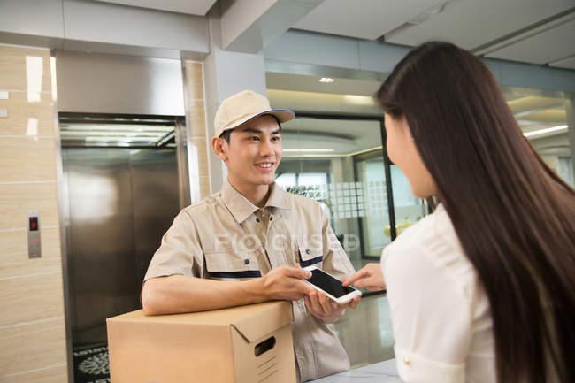 Улыбающийся молодой курьер с картонной коробкой смотрит на деловую женщину с помощью смартфона в офисе — стоковое фото