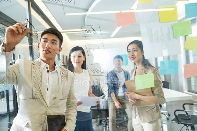 Blick durch das Glas junger asiatischer Geschäftsleute, die während eines Meetings im Büro Notizen machen — Stockfoto