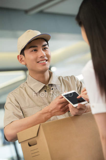 Cropped shot of smiling young courier with cardboard box looking at businesswoman using smartphone in office — Stock Photo