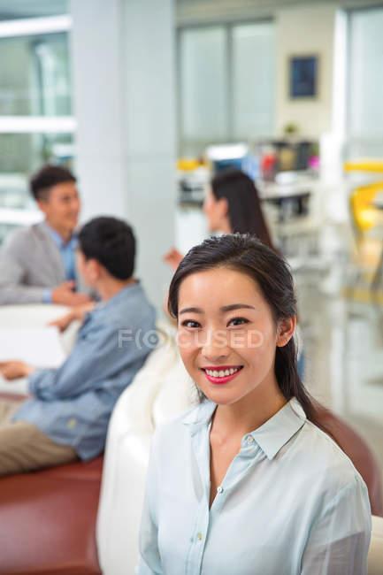 Красива молода Азіатська Ділова жінка посміхається на камеру, а колеги сидять в офісі — стокове фото