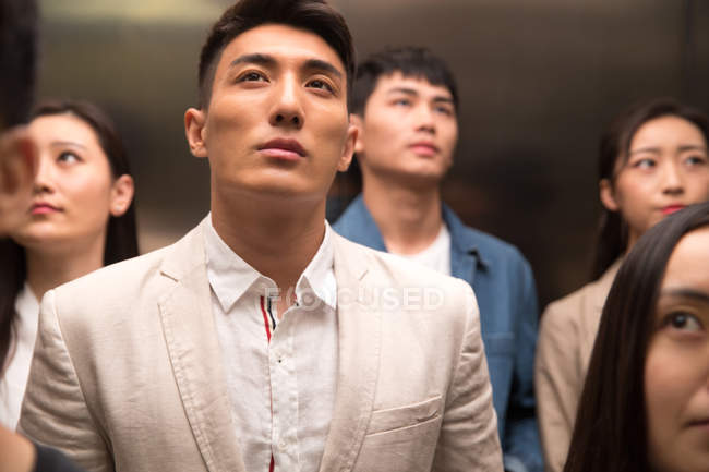 Young asian businessmen and businesswomen standing together in elevator — Stock Photo