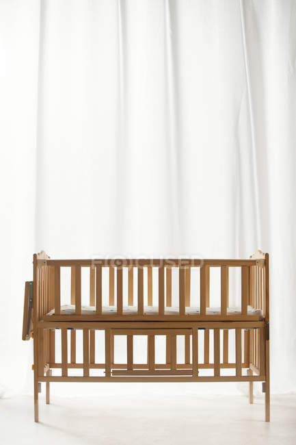Brown wooden baby bed in empty light room interior — Stock Photo