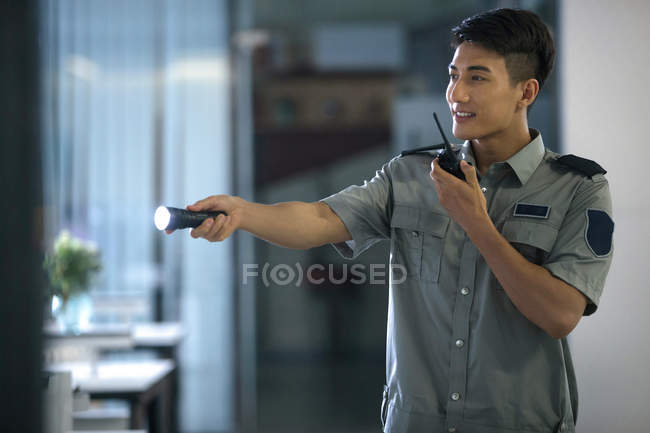 Smiling young security guard holding flashlight and using walkie-talkie in business center at night — Stock Photo