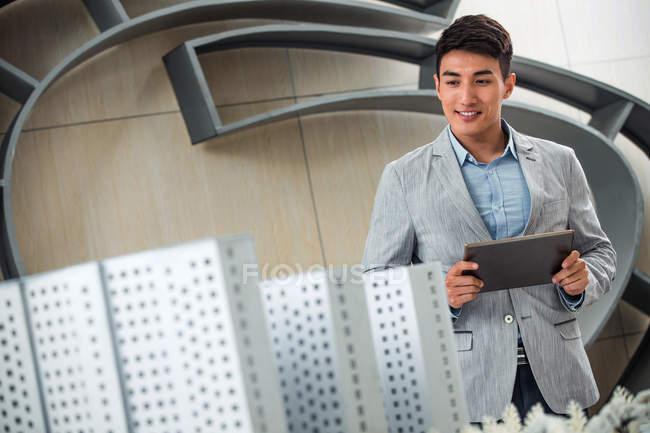 Посміхаючись молодий чоловічий архітектор проведення цифрової планшет і дивлячись на проект в офісі — стокове фото