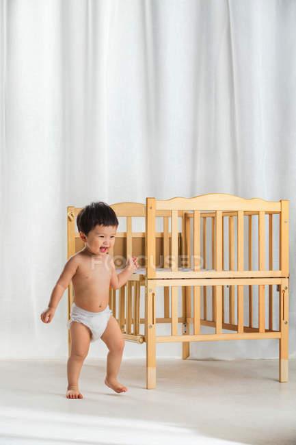 Adorable happy baby in diaper walking near crib in bedroom — Stock Photo