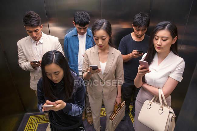 Vista ad alto angolo di giovani asiatici in piedi in ascensore e utilizzando smartphone — Foto stock